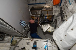 André Kuipers uses a vacuum cleaner on the Columbus ventilation systems (Credit: NASA)