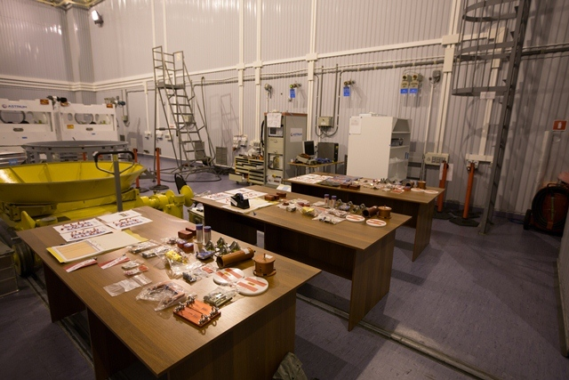 Red-tagged items for each satellite laid out on separate tables. (ESA/M. Shafiq)