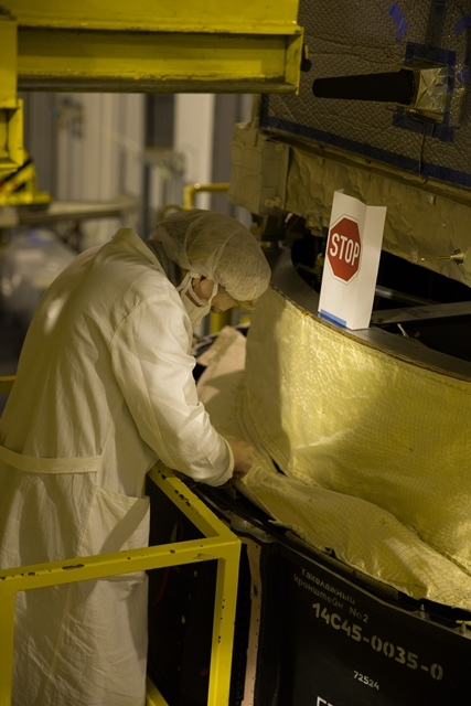 Sewing the last pieces of multilayer insulation around the base of the launch adapter. (ESA/M. Shafiq)