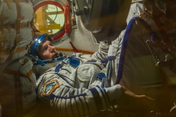 Andreas in Soyuz. Note cargo strapped to the left. Credits: Energia