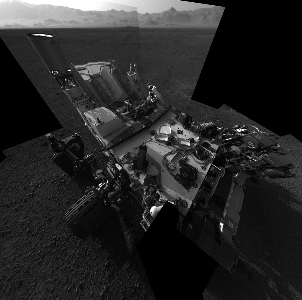 Still Life with Rover This full-resolution self-portrait shows the deck of NASA's Curiosity rover from the rover's Navigation camera. The back of the rover can be seen at the top left of the image, and two of the rover's right side wheels can be seen on the left. The undulating rim of Gale Crater forms the lighter color strip in the background. Bits of gravel, about 0.4 inches (1 centimeter) in size, are visible on the deck of the rover. Credit: NASA