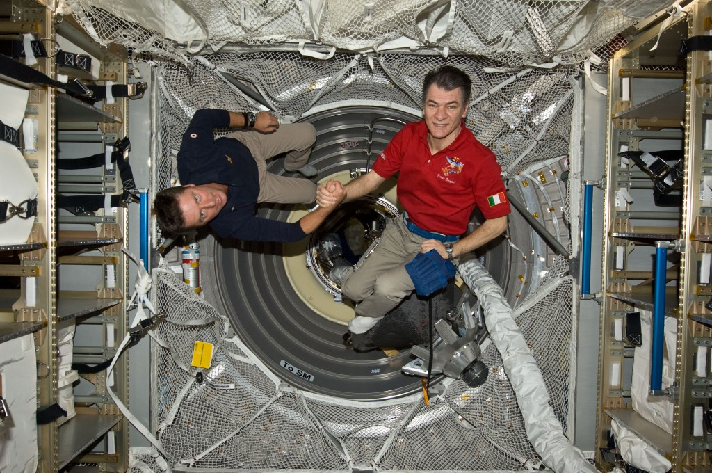 On 23 May 2011, ESA astronauts Paolo Nespoli (left) and Roberto Vittori shake hands inside the ATV following an Earth-to-space phone tag-up with Italian President Giorgio Napolitano. Credit: NASA