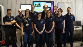 The team at ESOC at the end of the experiment. The screen at the back shows that the rover has returned to its original position and the network has successfully operated for 1hr 49min. Credit: ESA/L.Wellard