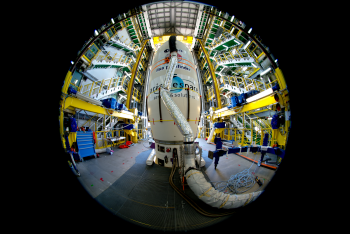 LISA Pathfinder ready for launch. Final preparations are under way at Europe's Spaceport in Kourou, French Guiana, for the launch of LISA Pathfinder, ESA's technology demonstrator that will pave the way for detecting gravitational waves from space. Liftoff is planned at 04:15 GMT (05:15 CET) on 2 December. In this image, taken with an ultra-wide angle fisheye lens on 19 November, the spacecraft is hidden from view, encapsulated in the 'upper composite' of its Vega rocket. Only the aerodynamic fairing at the top of the fully assembled launcher is visible, while the lower stages are hidden by the movable access platform. The hose is part of the air conditioning system that regulates the environment inside the fairing. Credit: ESA–M. Pedoussaut, 2015