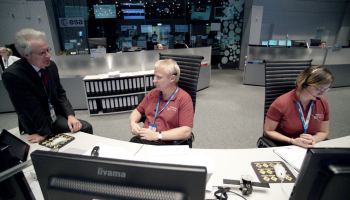 Spacecraft Operations Manager Peter Schmitz seen, sitting, at left, in discussion with ESA's Head of Mission Operations, Paolo Ferri, in the Main Control Room at ESOC just after ExoMars/TGO launch in March 2016. Deputy Operations Manager Silvia Sangiorgi sits on console at right. Credit: ESA/P. Shlyaev.