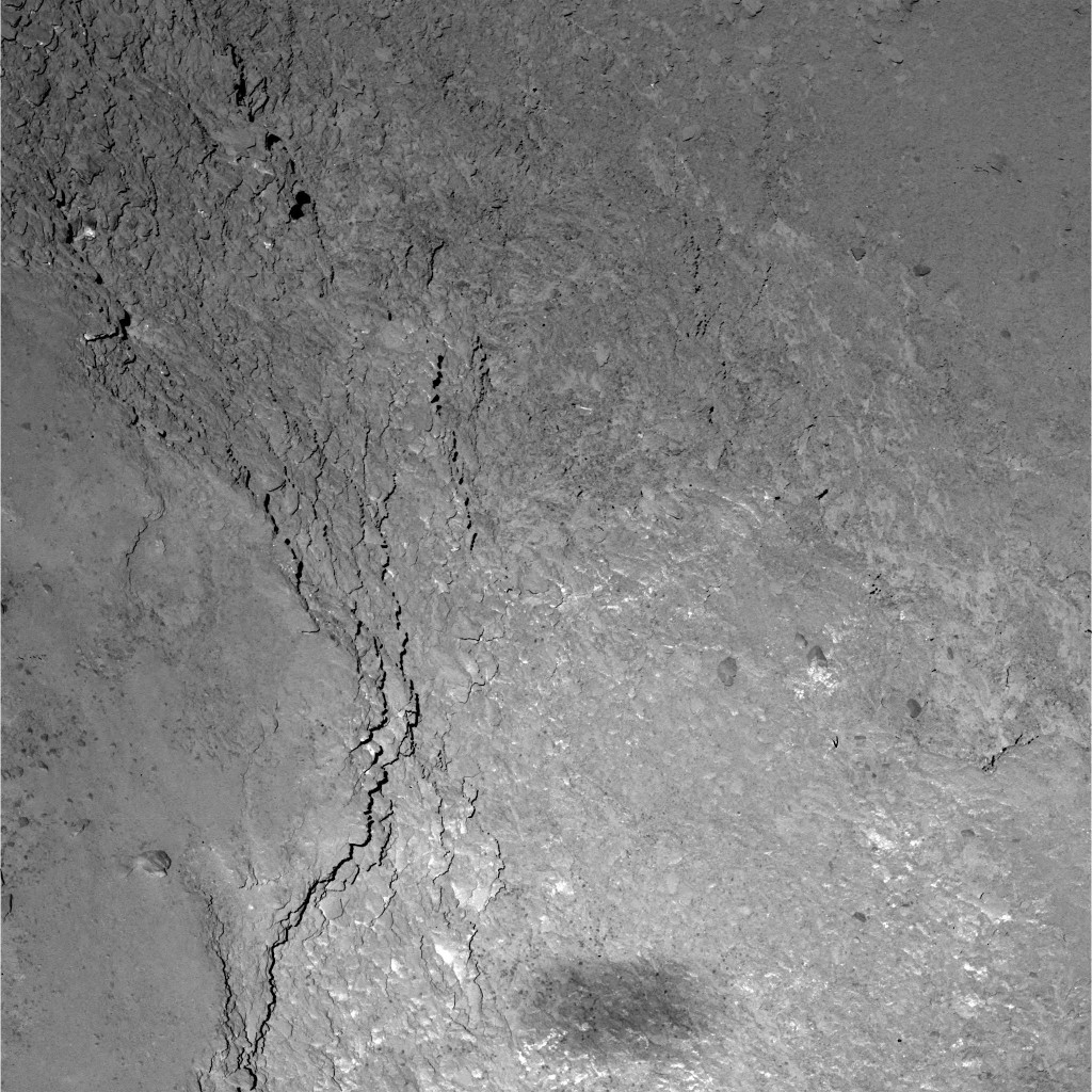 Close-up view of a 228 x 228 m region on the Imhotep region on Comet 67P/Churyumov-Gerasimenko, as seen by the OSIRIS Narrow Angle Camera during Rosetta's flyby at 12:39 UT on 14 February 2015. The image was taken six kilometres above the comet's surface, and the image resolution is just 11 cm/pixel. Rosetta's fuzzy shadow, measuring approximately 20 x 50 metres, is seen at the bottom of the image.