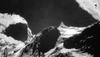 Images taken from just 8 km from the surface of Comet 67P/C-G are included in the latest NAVCAM release. This image was captured on 19 October 2014 and looks across the neck from the comet's small lobe in the foreground to the large lobe in the background. Parts of the Anuket and Serqet regions are visible in the foreground and a portion of Hapi is present at centre-left, with the dramatic cliff edge in Seth in the background. The average image scale (taking into account the variation in distance from the comet to Rosetta between the foreground and background) is approximately 77 cm/pixel, yielding an average frame width of 785m. Credits: ESA/Rosetta/NavCam – CC BY-SA IGO 3.0.