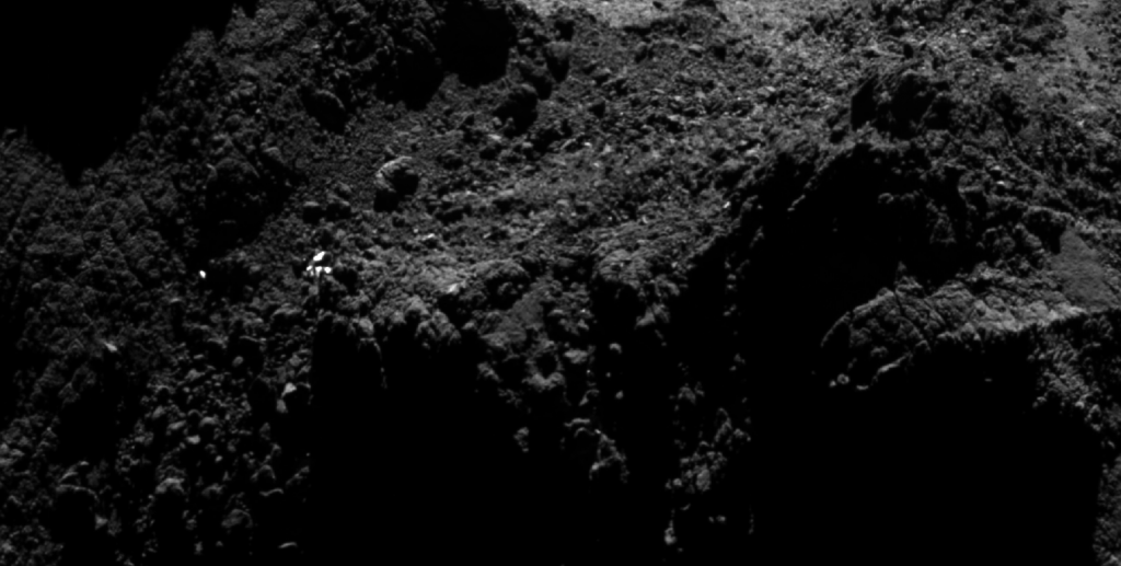 Zooming in towards the current CONSERT ellipse, a number of bright dots are seen in the region. As only one (at most) of these could be the lander, the majority must be associated with surface features on the comet nucleus.  Credits: ESA/Rosetta/MPS for OSIRIS Team MPS/UPD/LAM/IAA/SSO/INTA/UPM/DASP/IDA