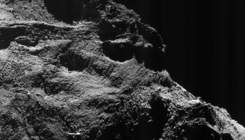 Enhanced NAVCAM view of Comet 67P/Churyumov-Gerasimenko, taken from a distance of 9.7 km on 24 July 2016. The image scale is 0.8 m/pixel and the image measures 0.9 km across. The faint vertical striping effect, especially visible in the upper right part of this view, is an image artifact. Credits: ESA/Rosetta/NAVCAM – CC BY-SA IGO 3.0