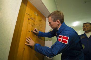 ESA astronaut Andreas Mogensen signs the door of his hotel room before launch September 2015. Credits: ESA