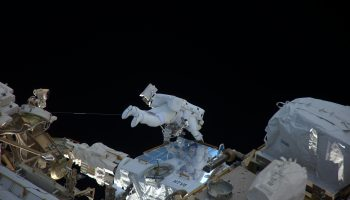 Thomas in same white spacesuit holding onto handrail during his first spacewalk. Credits: Roscosmos