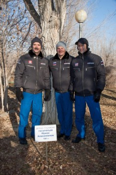 Astronauts pose in front of Yuri Gagarin's tree that was planted in 1961.