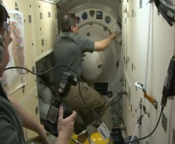 Closing the hatch. Credits: NASA